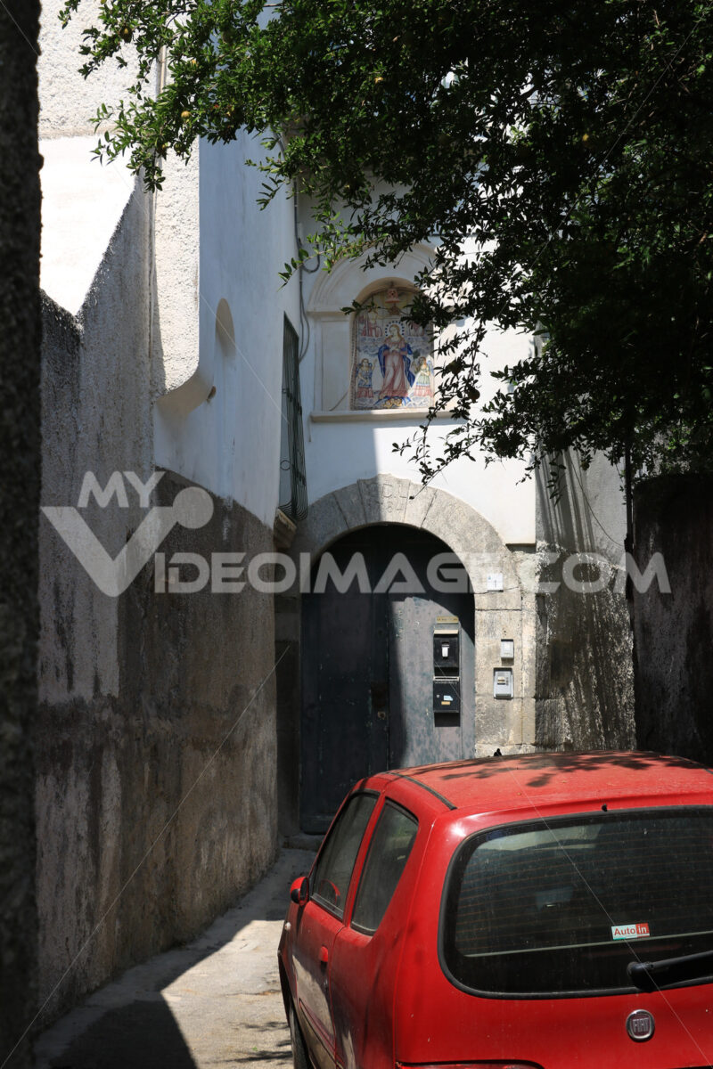 Narrow street in southern Italy with a small red car. Door with stone arched doors. Foto automobili. Cars photos.