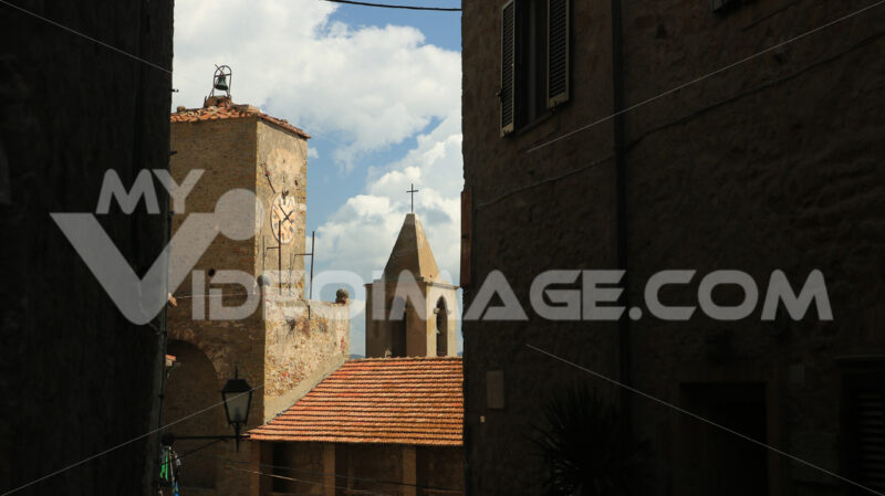 Narrow street with clock tower and bell tower in Castiglione della Pescaia. An ancient village in the Tuscan Maremma built on a hill facing the sea. - MyVideoimage.com | Foto stock & Video footage