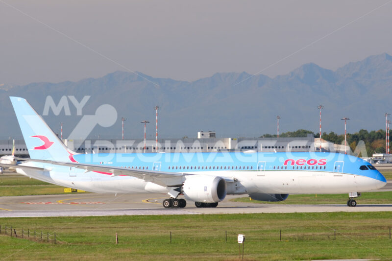 Neos Boeing 787-9 Dreamliner on the Malpensa airport runway. In the background the mountains of the Alps. - MyVideoimage.com