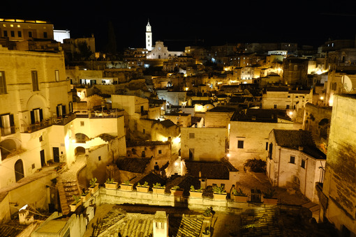 Night panorama of the city of Matera in Italy. Streets, church with bell tower and houses illuminated by artificial yellow lights. - MyVideoimage.com