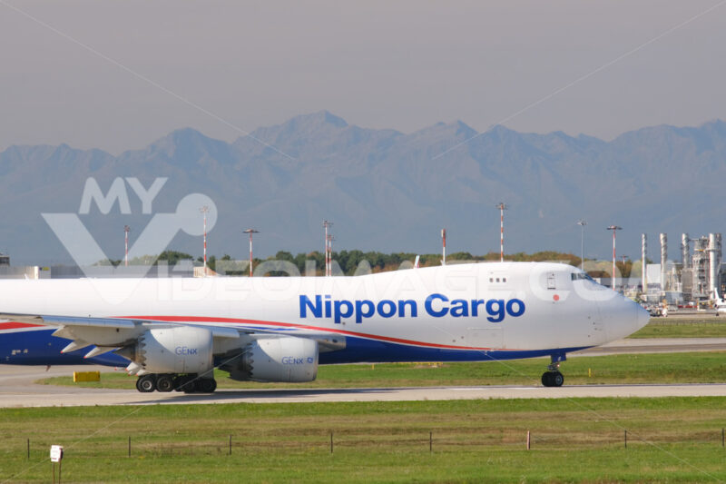 Nippon Cargo Boeing 747 on the Malpensa airport runway.  In the background the mountains of the Alps. - MyVideoimage.com