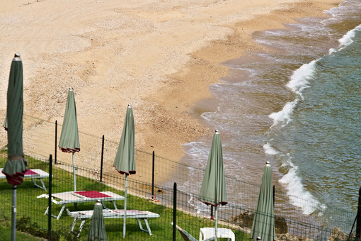 Ocher yellow beach and blue green sea. Closed umbrellas and sun loungers on green lawn. - MyVideoimage.com
