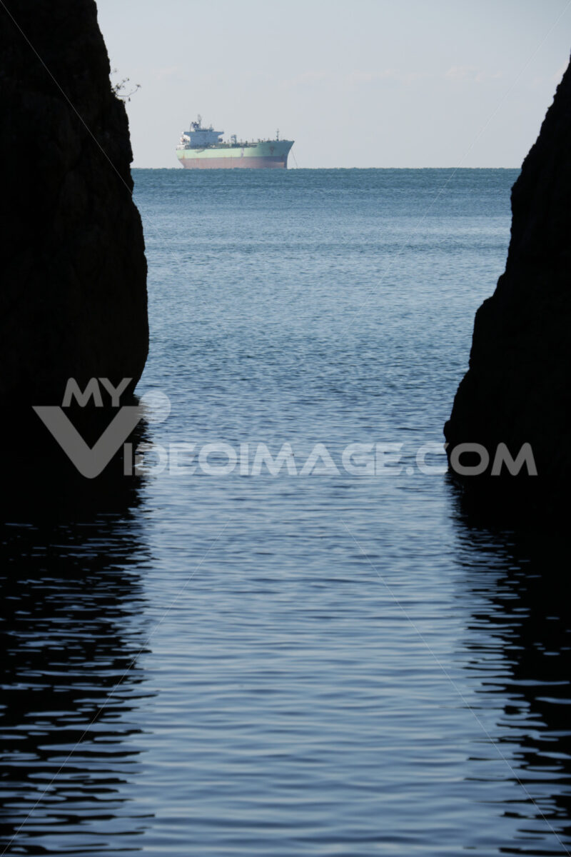 Oil tanker In the middle of the sea between two rocks. - MyVideoimage.com