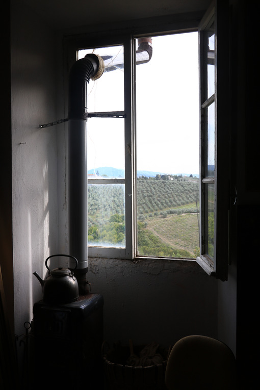 Old artist's studio window with the backdrop of the hills of Florence. In the foreground a charcoal stove with kettle placed on top. - MyVideoimage.com