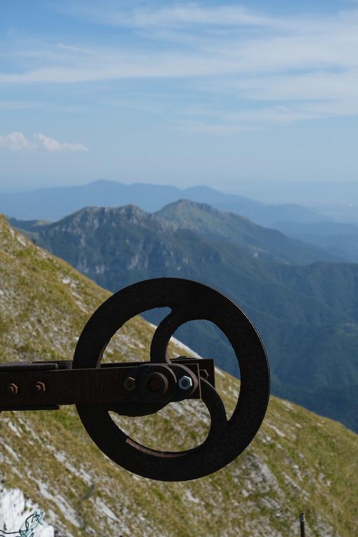 Old iron wheel. Alpine panorama on the Apuan Alps in Alta Versilia. Monte Corchia. Stock photos. - MyVideoimage.com | Foto stock & Video footage