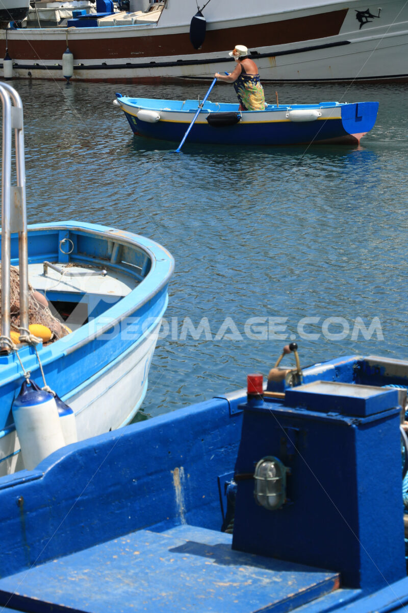 Old woman in a boat. Woman with rowing boat in the port of Corricella. - MyVideoimage.com | Foto stock & Video footage