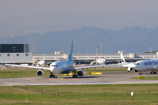 Oman Air Airbus A330-243  airplane on the Malpensa airport runway. In the background the buildings and Air Italy airplane. - MyVideoimage.com