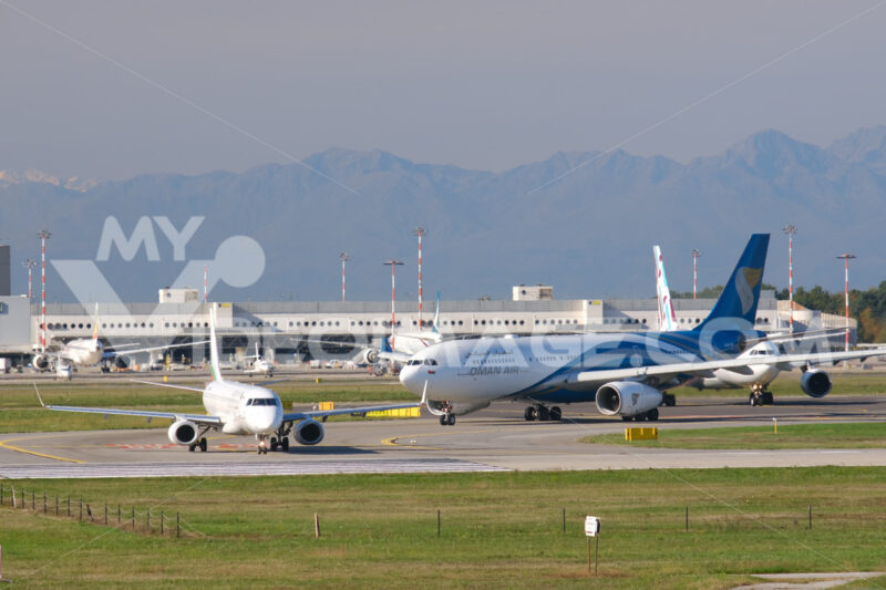 Oman Air Airbus A330-243  airplane on the Malpensa airport runway. In the background the buildings and Bulgaria Air Embraer 190/195 airplane. - MyVideoimage.com