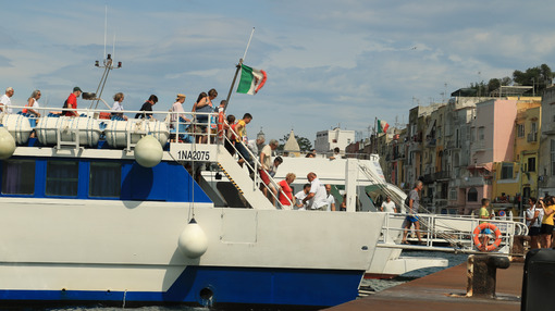 Ormeggio in porto. Small ship strolling at the port of Procida, Naples. Docking stage at the pier. People intent on landing. - MyVideoimage.com | Foto stock & Video footage