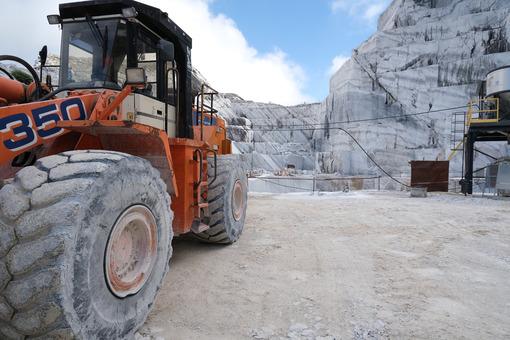 Pala gommata in cava di marmo. Wheel loader in a white marble quarry near Carrara. Foto stock royalty free. - MyVideoimage.com | Foto stock & Video footage