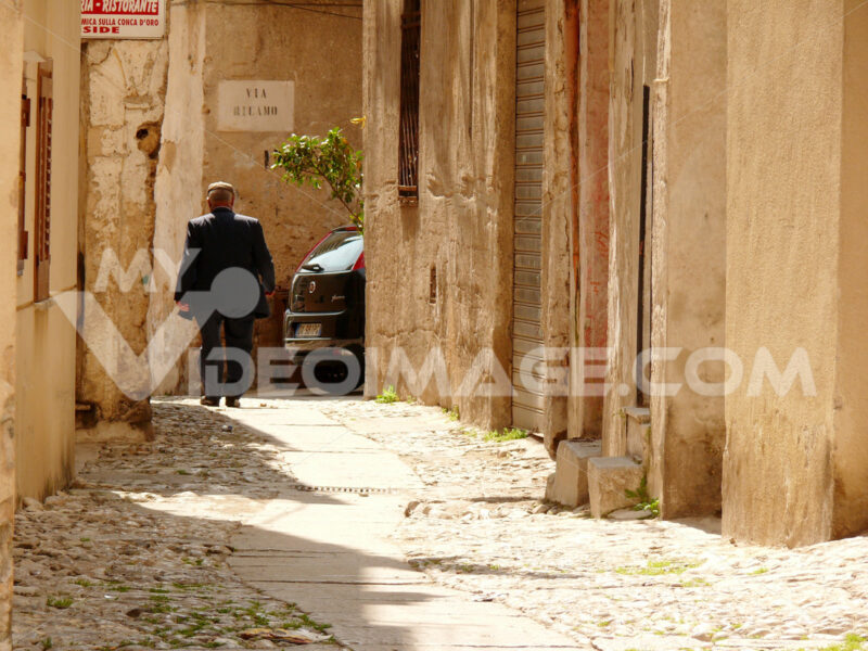 Palermo, Sicily, Italy. A Sicilian walks on a small street - MyVideoimage.com | Foto stock & Video footage