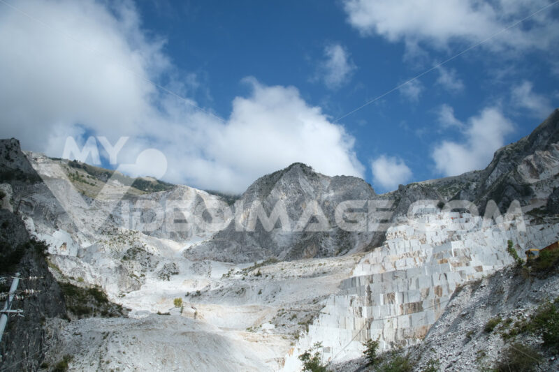 Panorama cave di marmo. Panorama of a white Carrara marble quarry in Tuscany. Mountains of the Apuan Alps, blue sky and cloud. - MyVideoimage.com | Foto stock & Video footage