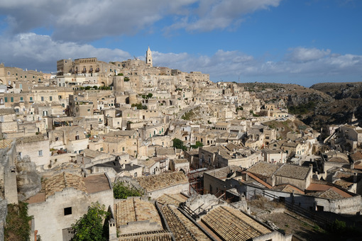 Panorama of houses and of the Sassi of Matera with roofs and streets. Blue sky with - MyVideoimage.com