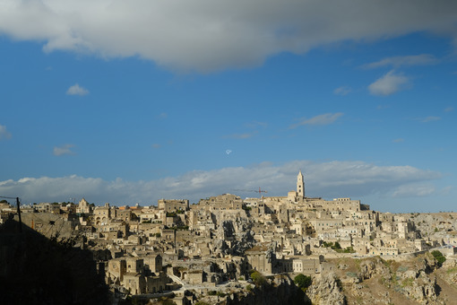 Panorama of houses and of the Sassi of Matera with roofs and streets. Blue sky with church and bell tower with blue sky background with clouds. - MyVideoimage.com