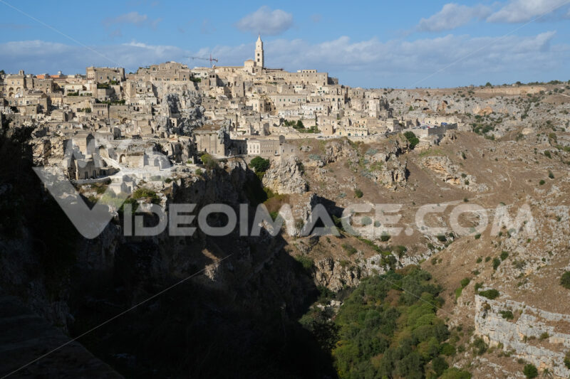 Panorama of houses and of the Sassi of Matera with roofs and streets. Blue sky with church and bell tower with blue sky background with clouds. - LEphotoart.com