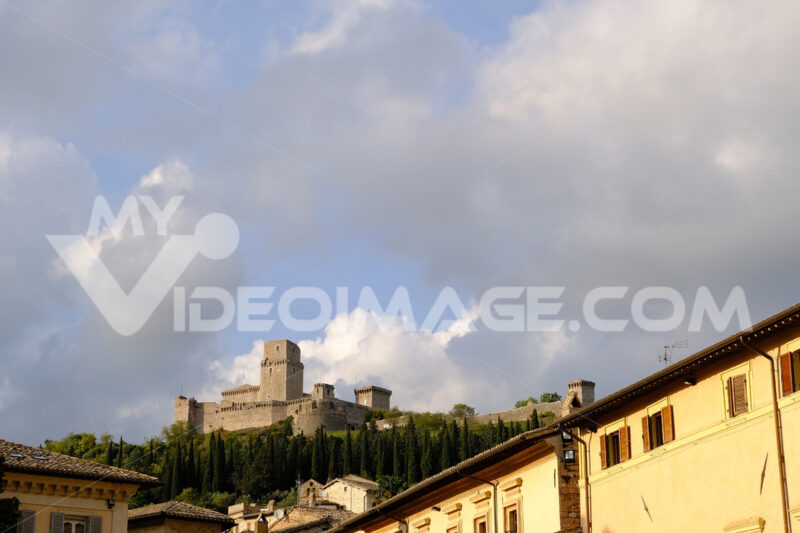 Panorama of the Rocca Maggiore castle in Assisi. The fortress illuminated at sunset immersed in a cypress wood. - MyVideoimage.com