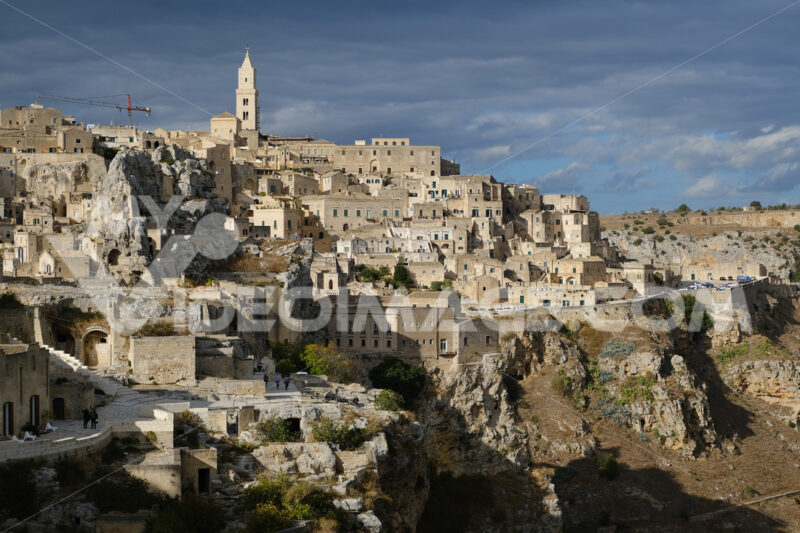 Panorama of the Sassi of Matera with houses in tuff stone. Church and bell tower at dawn with sky and clouds. - MyVideoimage.com