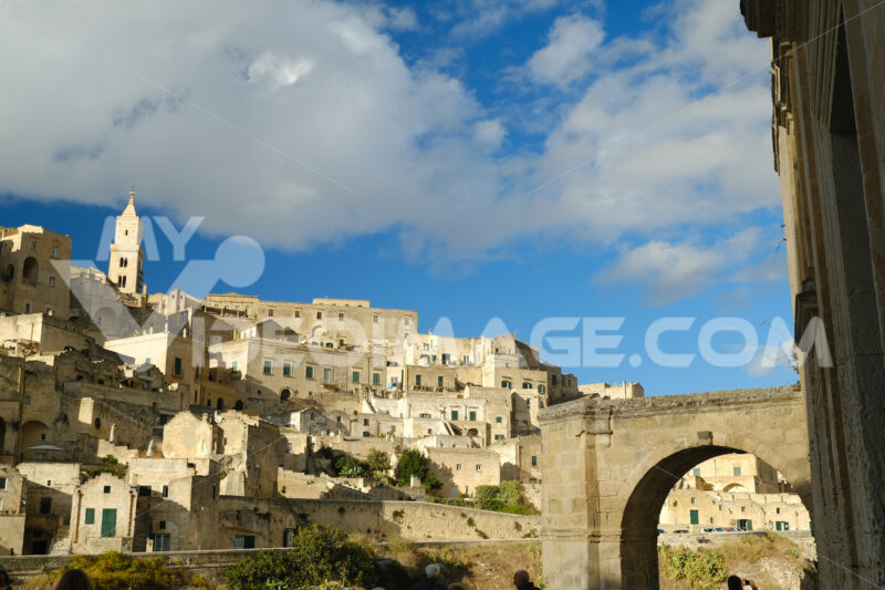 Panorama of the Sassi of Matera with houses in tuff stone. Church with bell tower and stone arch at dawn with sky and clouds. - MyVideoimage.com