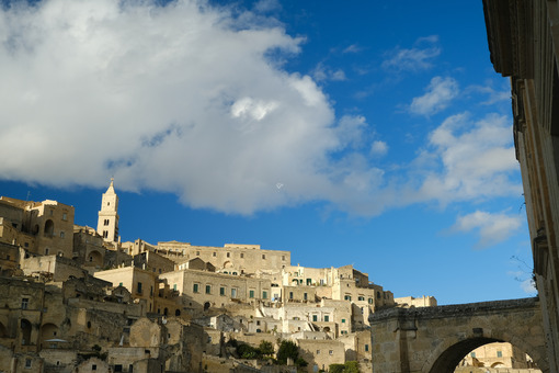Panorama of the Sassi of Matera with houses in tuff stone. Church with bell tower and stone arch at dawn with sky and clouds. - LEphotoart.com
