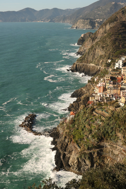 Panorama of the village of Riomaggiore in the Cinque Terre. Rough sea with waves on the cliff. - MyVideimage.com