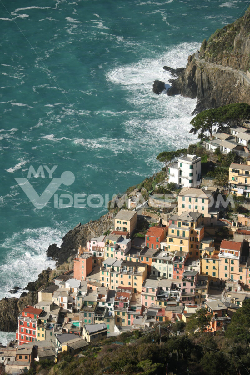Panorama of the village of Riomaggiore in the Cinque Terre. Rough sea with waves on the cliff. - LEphotoart.com