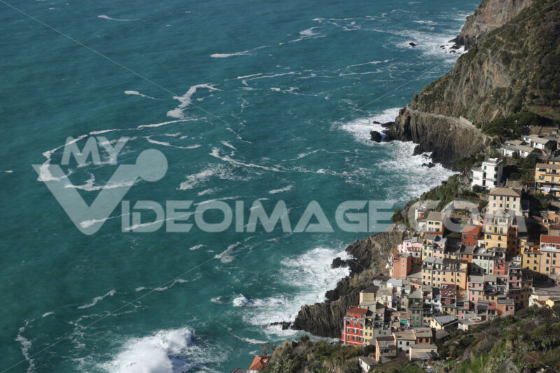 Panorama of the village of Riomaggiore in the Cinque Terre. Rough sea with waves on the cliff. - MyVideoimage.com