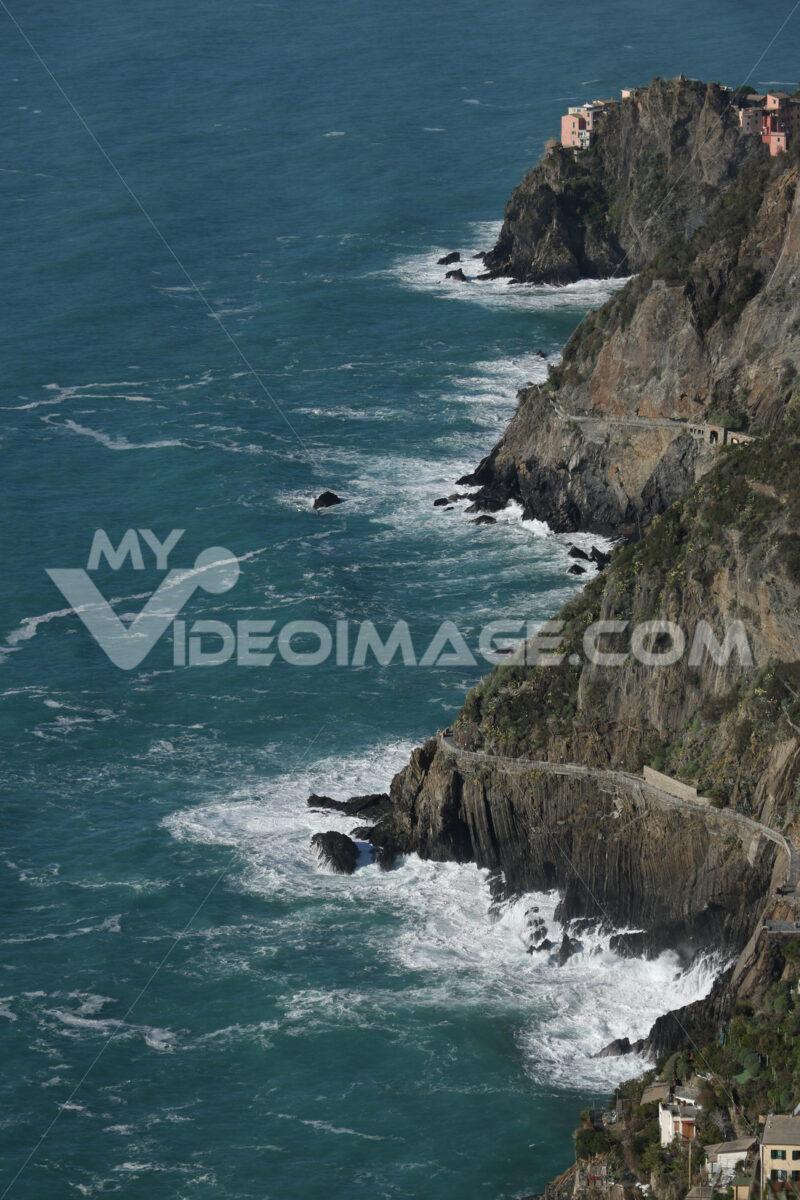 Panorama of the village of Riomaggiore in the Cinque Terre. Rough sea with waves on the cliff. Foto sfondo mare. - MyVideoimage.com