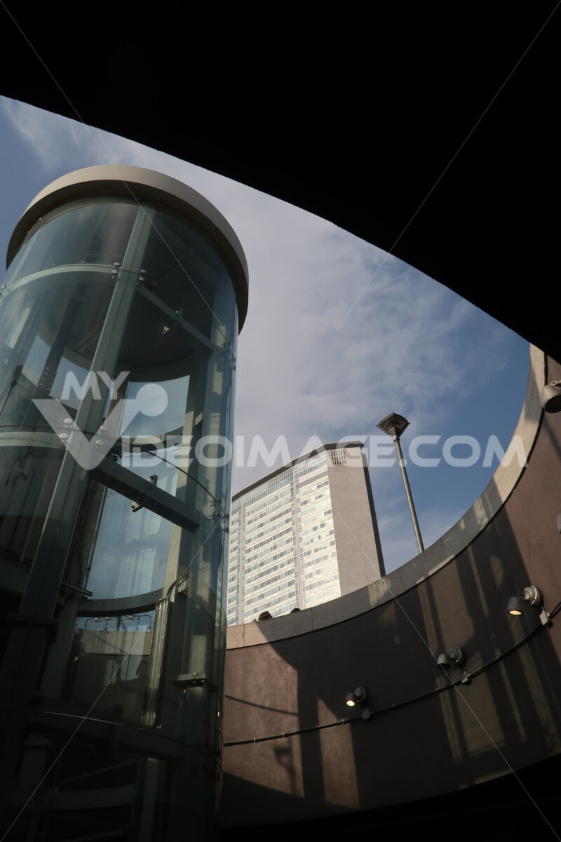 Panoramic lift with glass facade. In the background the Pirelli skyscraper in Milan. Central Station. - MyVideoimage.com