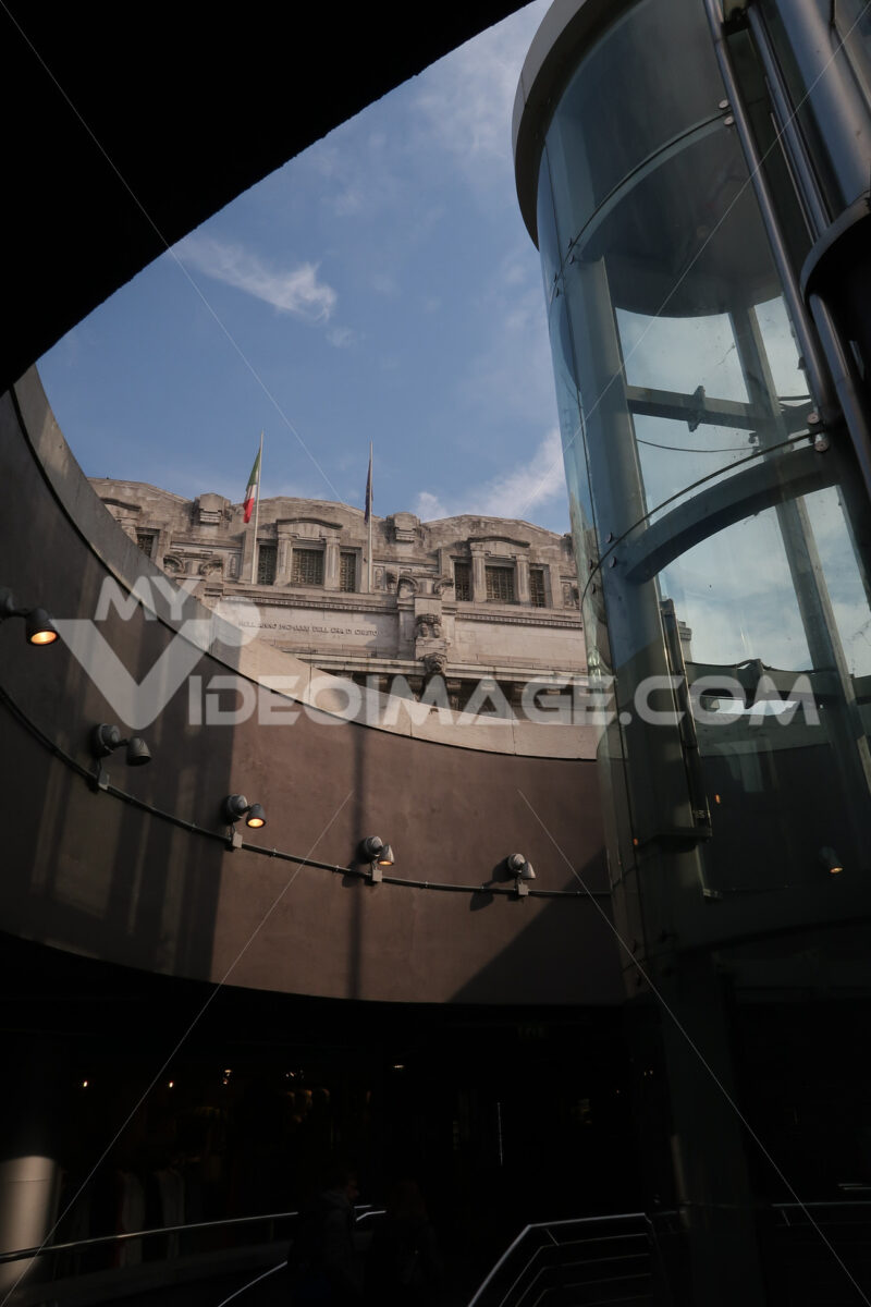 Panoramic lift with glass facade. In the background the central station of Milan in imperial neoclassical style. - MyVideoimage.com