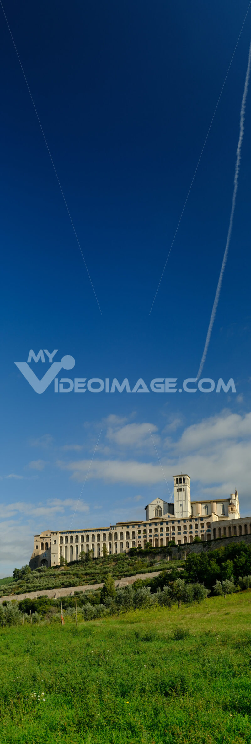 Panoramic photo of the convent and church of San Francesco in Assisi. The architecture immersed in the countryside with cultivation of olive trees. - MyVideoimage.com | Foto stock & Video footage