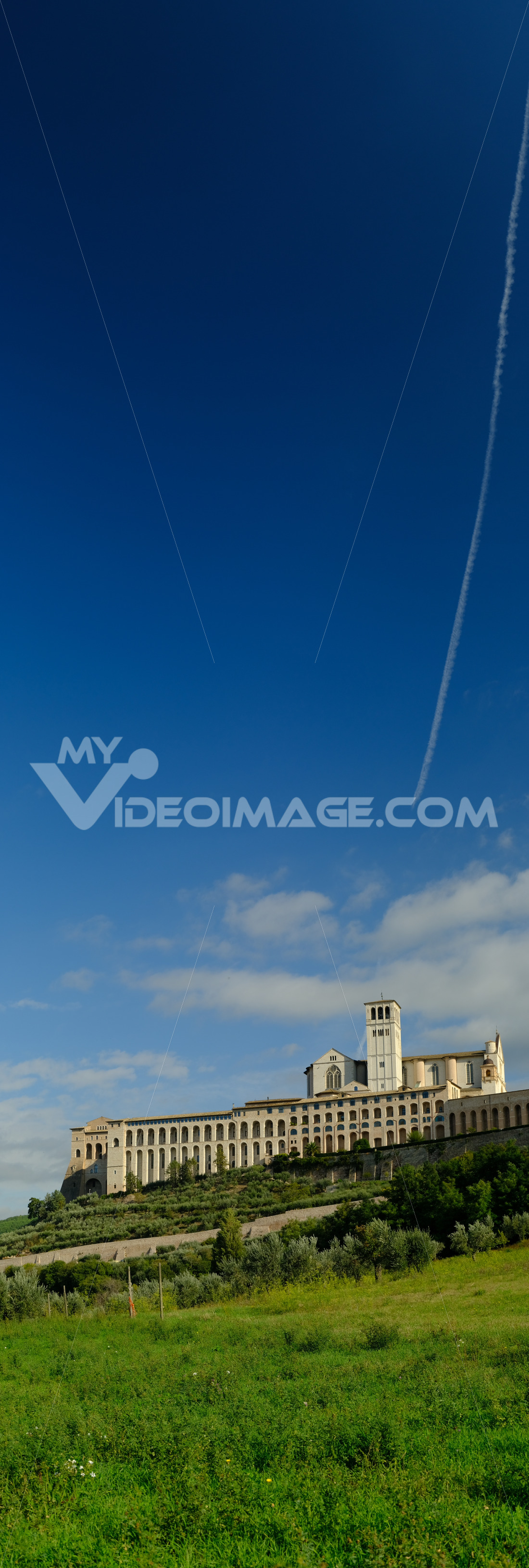Panoramic photo of the convent and church of San Francesco in Assisi. The architecture immersed in the countryside with cultivation of olive trees. - MyVideoimage.com