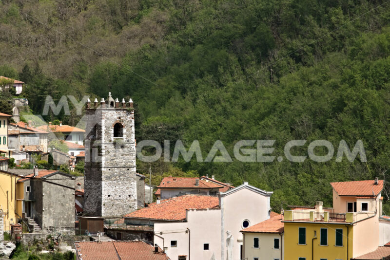 Panoramic shot of the village of Colonnata, where the famous lard is produced. The walls of the houses in stone and white Carrara marble. Woods background. Northern Tuscany. Colonnata, Carrara, Italy. - MyVideoimage.com