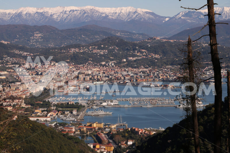 Panoramic view of La Spezia in Liguria shot from above. A cruise ship in the port, numerous moored sailboats and commercial port cranes. - MyVideoimage.com
