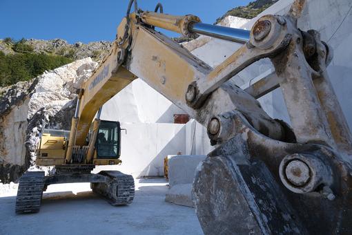 Parete di marmo bianco in cava. Crawler excavator in a marble quarry near Carrara. Foto stock royalty free. - MyVideoimage.com | Foto stock & Video footage