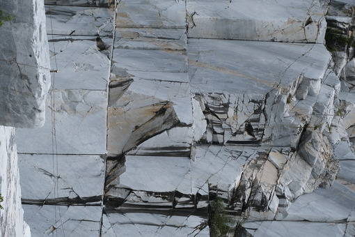 Parete di marmo bianco in cava. Wall of a white marble quarry under the mountain. Foto stock royalty free. - MyVideoimage.com | Foto stock & Video footage