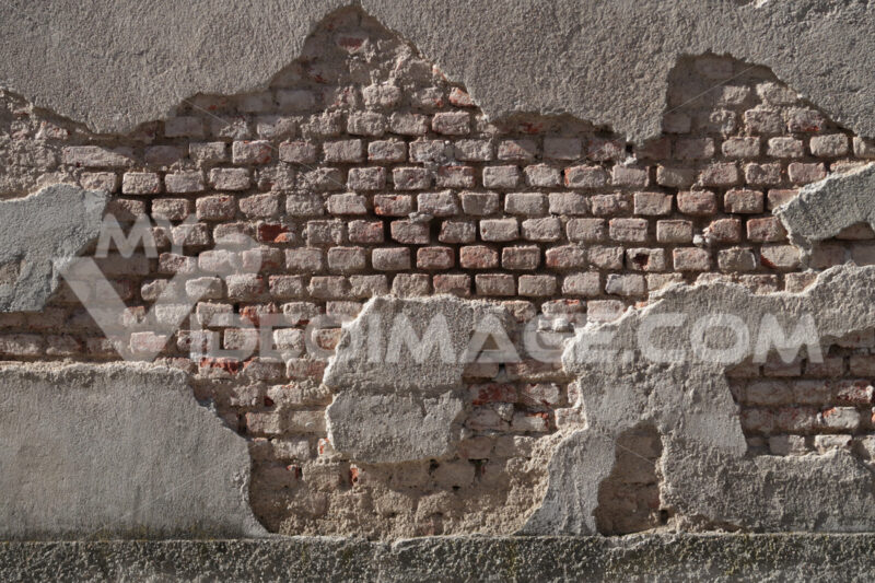Peeling wall. A partly plastered brick wall. The humidity of the wall caused part of the plaster to fall off the wall. - MyVideoimage.com | Foto stock & Video footage