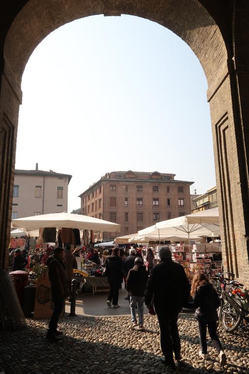People at the Parma market in Piazza della Pace. Brick arch of the Palazzo della Pilotta. - MyVideoimage.com