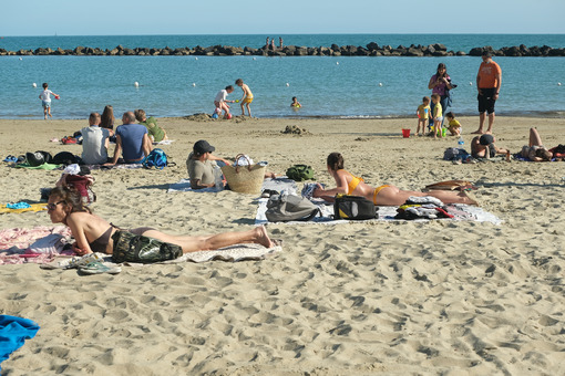 People lying in the sun. People lying on the beach of a village in Liguria. Stock photos. - MyVideoimage.com | Foto stock & Video footage