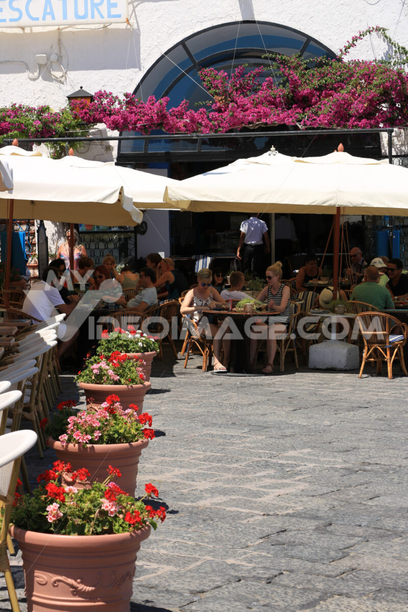People sitting at an outdoor bar under an umbrella. Row of pots - MyVideoimage.com