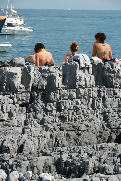 People stretched out sunbathing on the cliffs of the Tino Island, in the Gulf of La Spezia, near the Cinque Terre. - MyVideoimage.com
