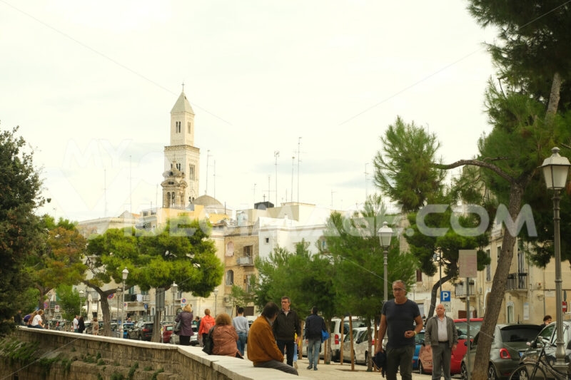 People walking in a street of the city of Bari. In the background the church bell tower. Foto Bari photo.