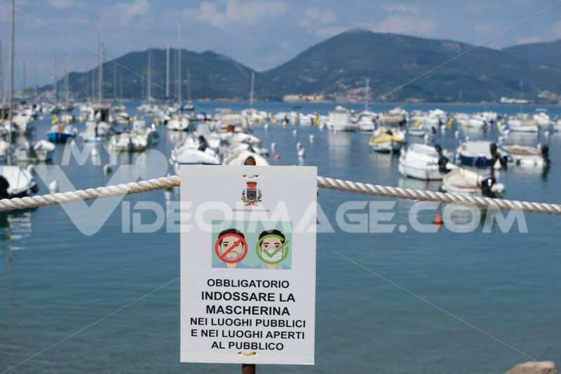 Period of Covid 19, warning signs with the sea in the background and the inscription. - MyVideoimage.com | Foto stock & Video footage
