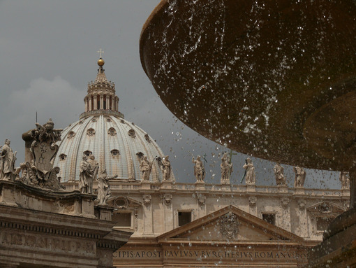Piazza San Pietro fountain in Rome with the dome and a detail of the church. - MyVideoimage.com