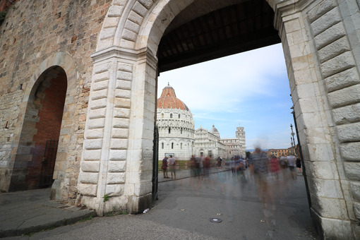 Piazza dei Miracoli of Pisa seen from a door of the city walls. The tower and the cathedral can be seen from the white marble portal. - MyVideoimage.com