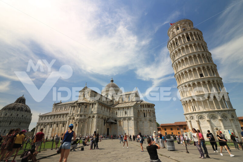 Piazza dei miracoli of Pisa. Travelers admire architecture. Cathedral, leaning tower of the Tuscan city. Blue sky with clouds. - MyVideoimage.com
