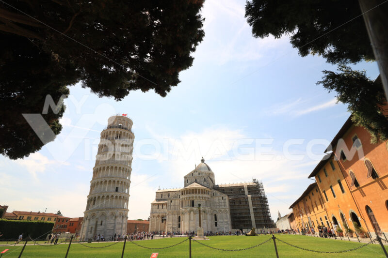 Piazza dei miracoli of Pisa. Travelers admire architecture. Cathedral, leaning tower of the Tuscan city. Blue sky with clouds. - LEphotoart.com