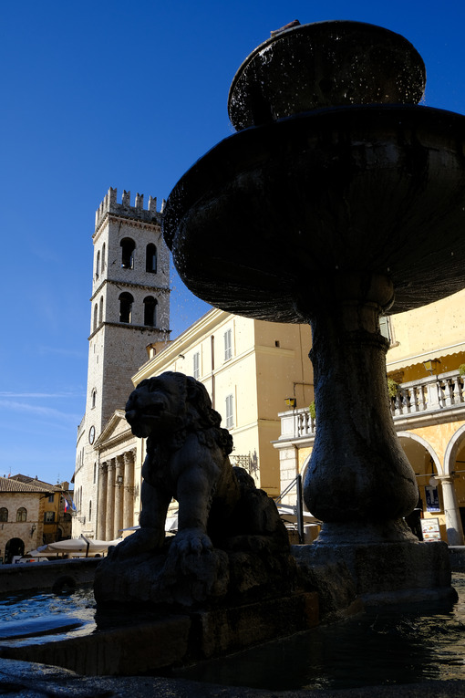 Piazza del Comune in Assisi with a stone fountain, civic tower and temple of Minerva. - LEphotoart.com