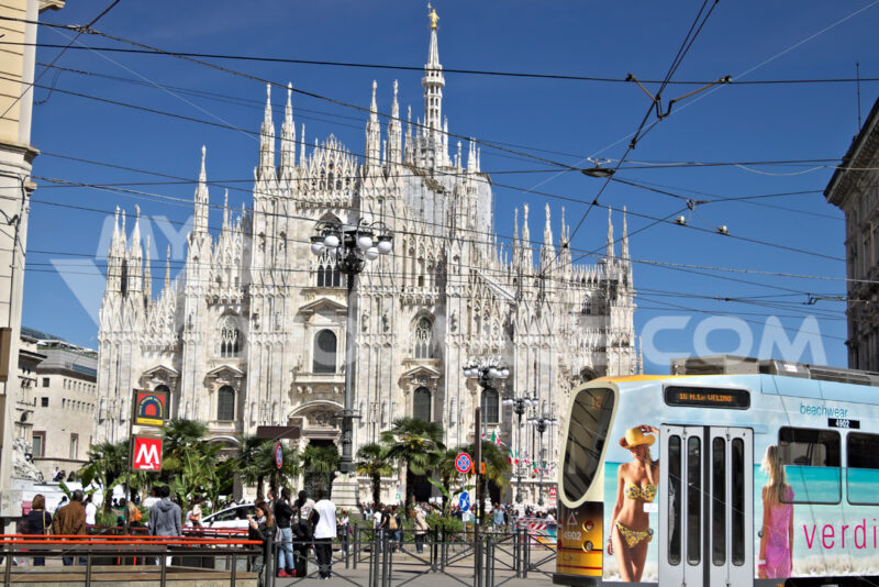 Piazza del Duomo in Milan with people and trams. The facade of the cathedral. In the foreground people walking and a multicolor tram. - MyVideoimage.com