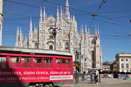 Piazza del Duomo in Milan with people and trams. The facade of the cathedral. In the foreground people walking and a yellow tram. - LEphotoart.com