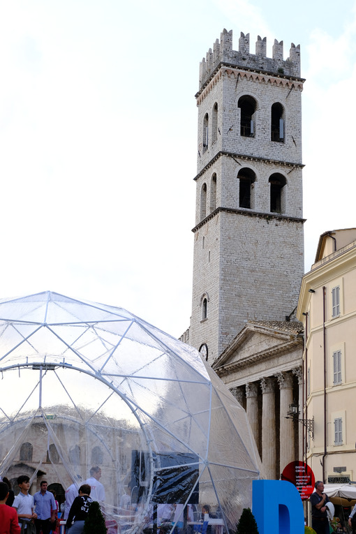 Piazza del comune di Assisi with the civic tower, the temple of Minerva and a geodesic dome with a reticular structure. - MyVideoimage.com